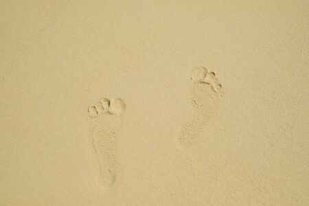 Footprints of a man walking on the sand beach.