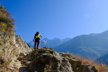 Trekker hiking with trekking pole on the mountain in Yunnan, China. Imagens