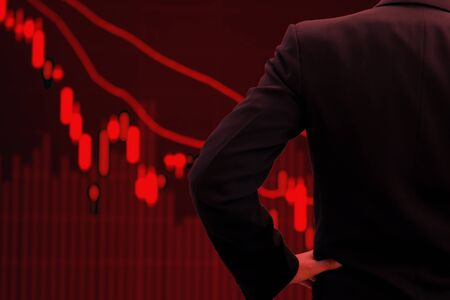 World economy and business in crisis concept. Red tone businessman watching stock market collapse.