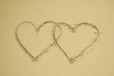 Two hearts drawn on the sand beach representing love, valentine, romance.