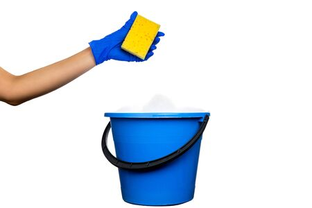 Plastic blue water bucket with soapsuds and black handle. Cleaning Products and Supplies. Gloved hand with sponge and soapy foam. Isolated white background