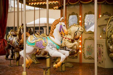 merry go round carousel with white horse closeup, winter 免版税图像