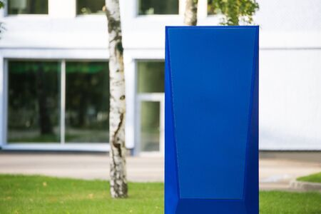 Blue information stand close - up in the Park on a blurred background of buildings and trees.