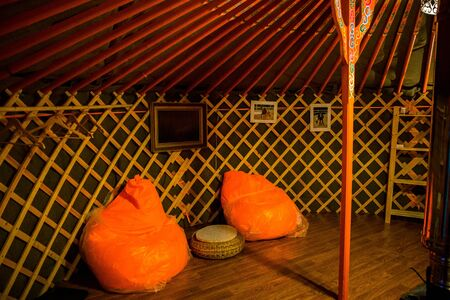 Upholstered furniture, sofa, Ottomans. Interior in Mongolian Yurt inside. Decorative details close up. Sedentary lifestyle, cattle breeding