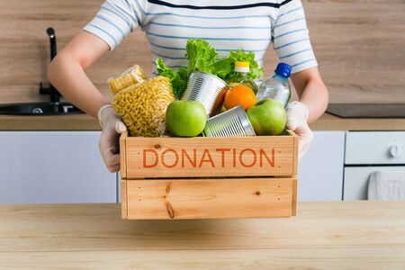 A girl in medical gloves dial charity donation crate box with food: oil, water, herbs, apples and fruits, cereals and canned food, rice, pasta. White wooden kitchen background. Close up