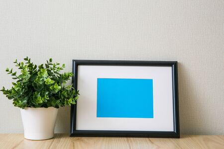 Mockup of a black horizontal photo frame with Passepartout. The light interior in the Scandinavian style. Composition on the table, shelf. Green plant in a white pot