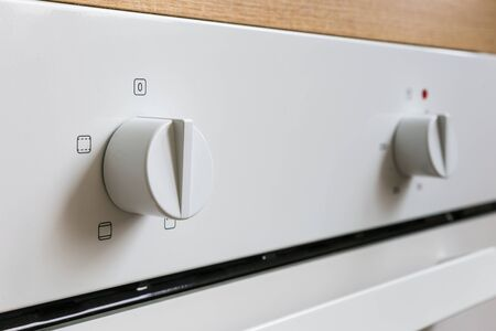 White electric oven switches. Control knobs for modern kitchen appliances. Close-up, at an angle in perspective