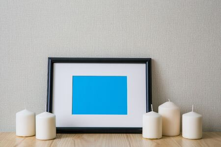 Mockup of a black horizontal photo frame with Passepartout. The light interior in the Scandinavian style. Composition on the table, shelf. White candles