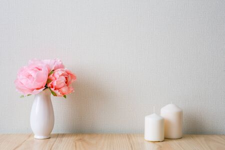 The light interior in the Scandinavian style. Composition on the table, shelf. Pink peonies in a white vase, white candles