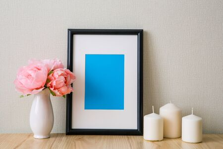 Mockup of a black vertical photo frame with Passepartout. The light interior in the Scandinavian style. Composition on the table, shelf. Pink peonies in a white vase, white candles Фото со стока