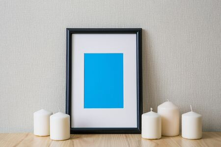 Mockup of a black vertical photo frame with Passepartout. The light interior in the Scandinavian style. Composition on the table, shelf. White candles Standard-Bild