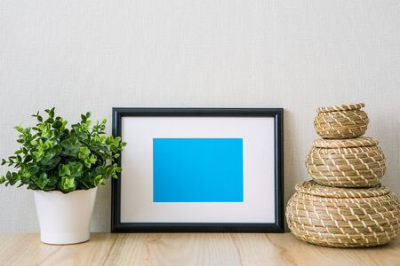 Mockup of a black horizontal photo frame with Passepartout. The light interior in the Scandinavian style. Composition on the table, shelf. Green plant in a white pot, wicker round baskets Standard-Bild