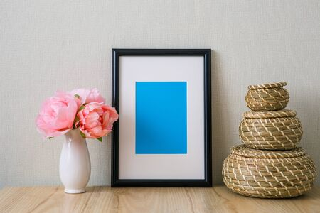 Mockup of a black vertical photo frame with Passepartout. The light interior in the Scandinavian style. Composition on the table, shelf. Pink peonies in a white vase, wicker round baskets Фото со стока
