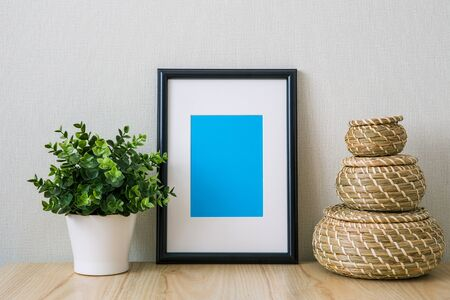 Mockup of a black vertical photo frame with Passepartout. The light interior in the Scandinavian style. Composition on the table, shelf. Green plant in a white pot, wicker round baskets