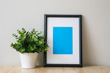 Mockup of a black vertical photo frame with Passepartout. The light interior in the Scandinavian style. Composition on the table, shelf. Green plant in a white pot