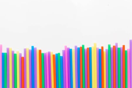 A strip of many plastic colored straws arranged in a row. Isolated on a white background
