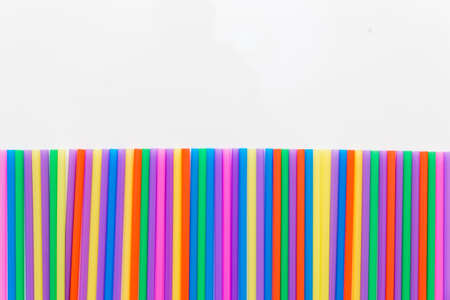 A strip of many plastic colored straws arranged in a row. Isolated Stockfoto