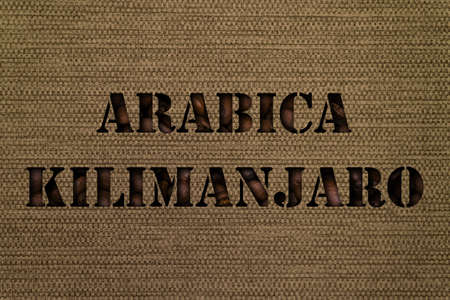 Variety Kilimanjaro Arabica text made up of coffee beans on a canvas background from a bag Foto de archivo