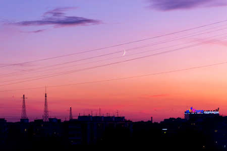 Pink orange purple sunset over the city. Multicolored sky and black silhouette of tall buildings of the metropolis. Radio towers and TV antennas. Gentle sky and the moon