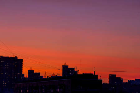 Pink orange purple sunset over the city. Multicolored sky and black silhouette of tall buildings of the metropolis Archivio Fotografico