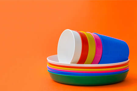 Children's unbreakable multicolored dishes, serving for a children's holiday. Isolated on an orange background