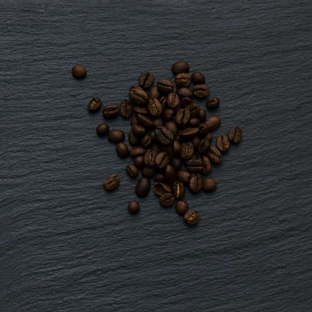 Lots of coffee beans on a black textured background of slate stone. Copy space for text