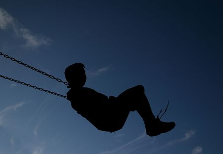 Child swinging in silhouette
