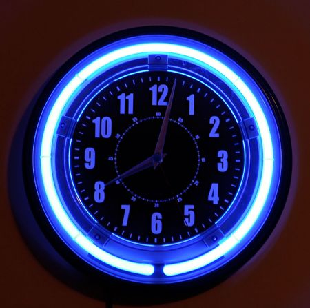 A blue neon clock hanging on the wall.