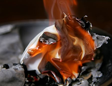 burning paper: ball of burning paper among the ashes with flames