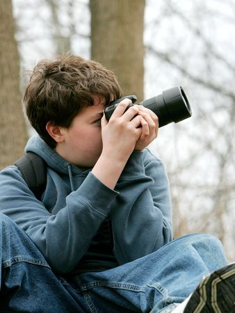 young teen boy taking photographs with his camera in the woods