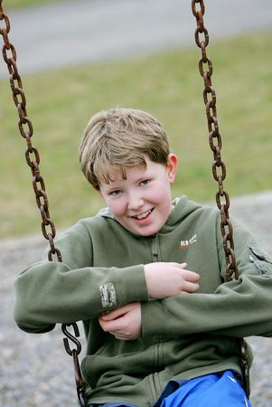 smiling male child playing and swinging on the playground photo