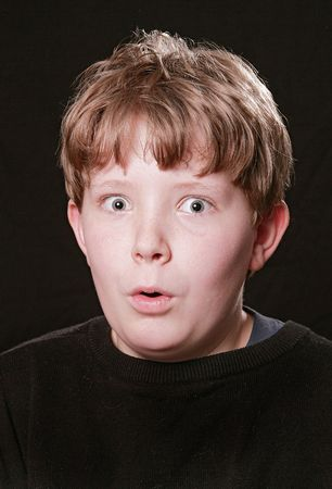 shocked young boy with wide eyes over black background photo