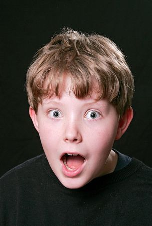shocked guy with wide eyes and open mouth close up facial expression over black photo