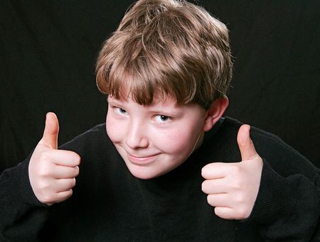 young kid giving happy two thumbs up expression of approval Stock Photo