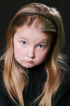 young chlid looking upset over a black background photo