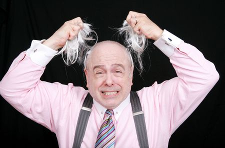 stressed out business man pulling his hair from his head frustrated and angry photo