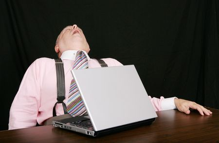 business man sleeping on the job while working at his laptop over black