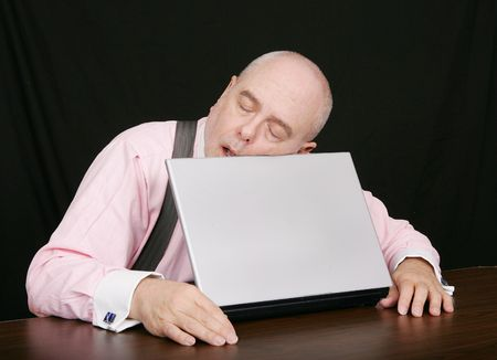 snore: business man sleeping on the job while working at his laptop over black