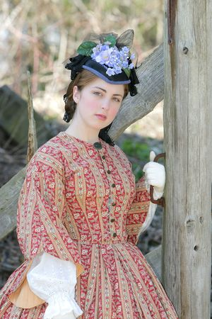 historische: Outdoor portret van een aantrekkelijk jong meisje in een burgerlijke Oorlog 1860 jurk