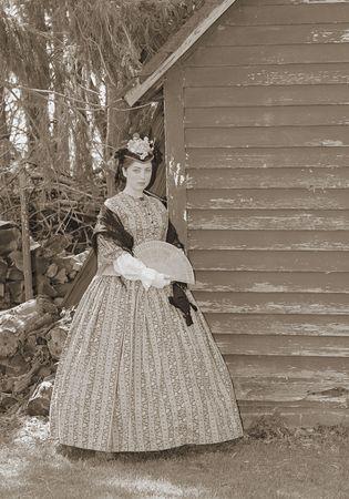 outdoor sepia portrait of an attractive young girl in a Civil War era 1860s dress Standard-Bild