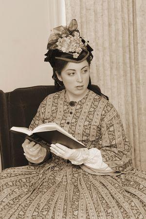 restored: sepia toned photo of reenactor playing young civil war era woman reading a book Stock Photo
