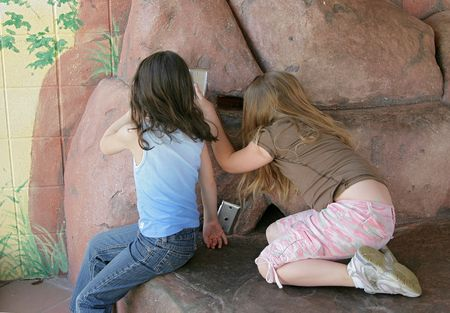 two children peeking in a hole at the zoo Stock Photo