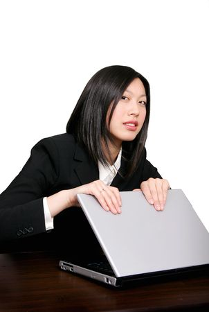 young beautiful asian girl protecting her computer from corporate theft or hiding her screen from the boss photo