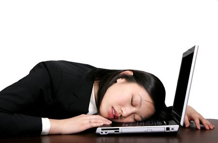 young asian woman sleeping on her computer photo