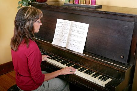 upright piano: 34 view of a women in red playing an upright piano Stock Photo