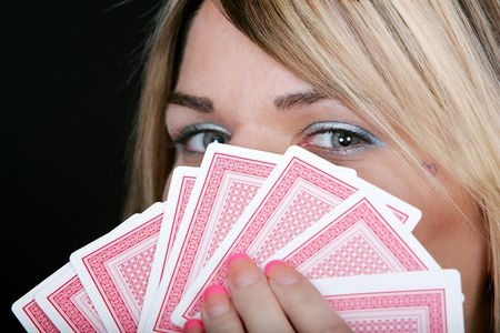 a sexy woman holding playing cards hiding her face