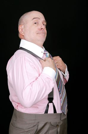 dapper: a middle aged man in a pink shirt on a black background