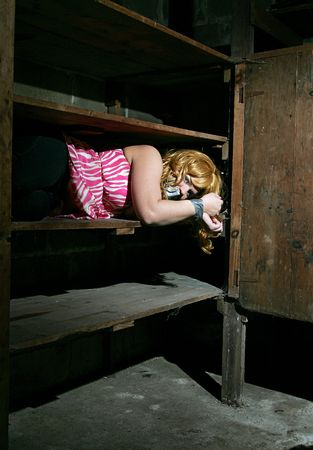 dank: a young adult female stored away by kidnappers tied up on a shelf Stock Photo