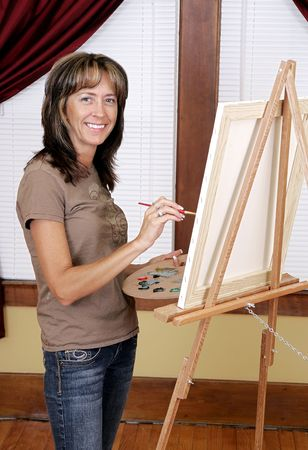 a woman smiling while painting a picture on her blank white canvas Banque d'images