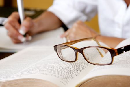a womans hand writing notes with eyeglasses on the book Stok Fotoğraf